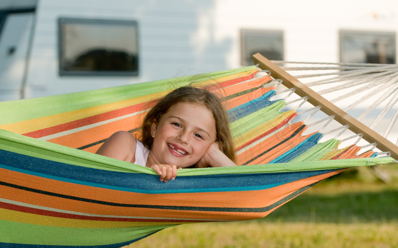Child smiling in hammock in front of RV.