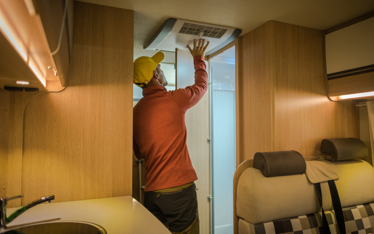 Man upgrading RV air conditioner inside the rig