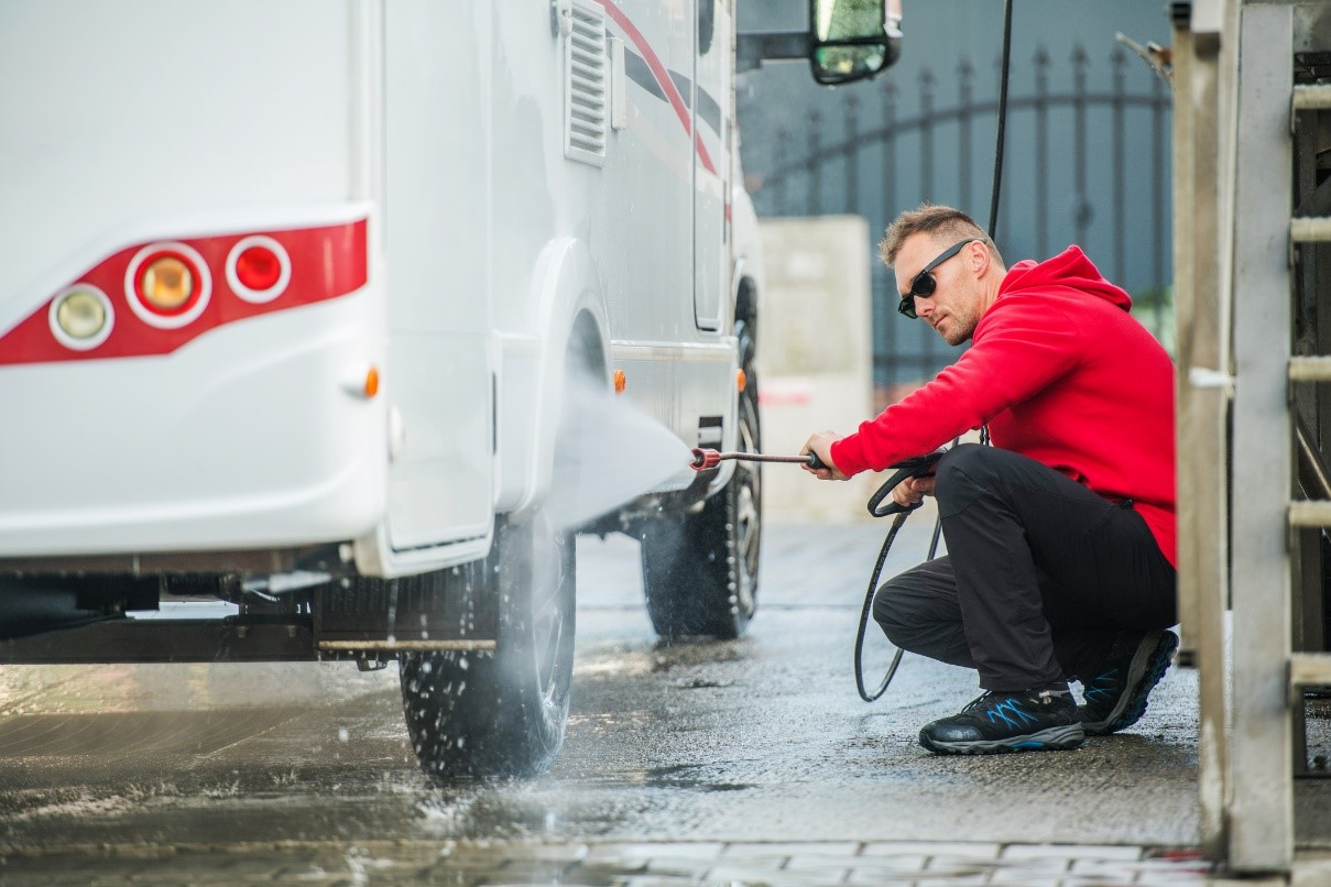 RVer cleaning the outside of his RV with a power washer