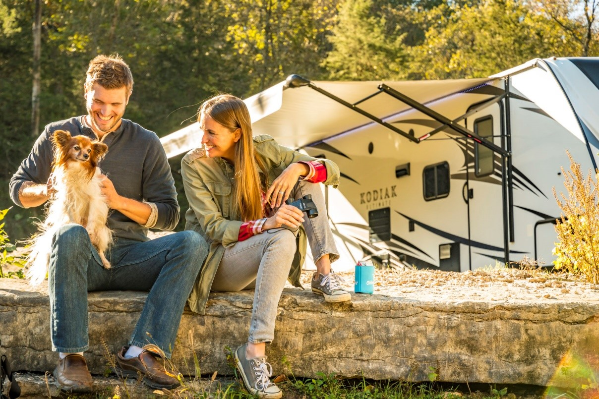 Couple sitting in front of their RV with their small dog