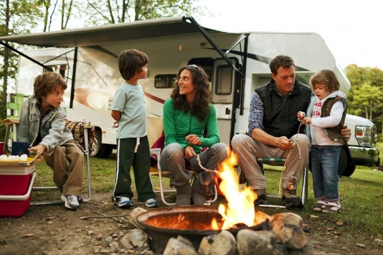 Family enjoying a campfire next to their Class C RV