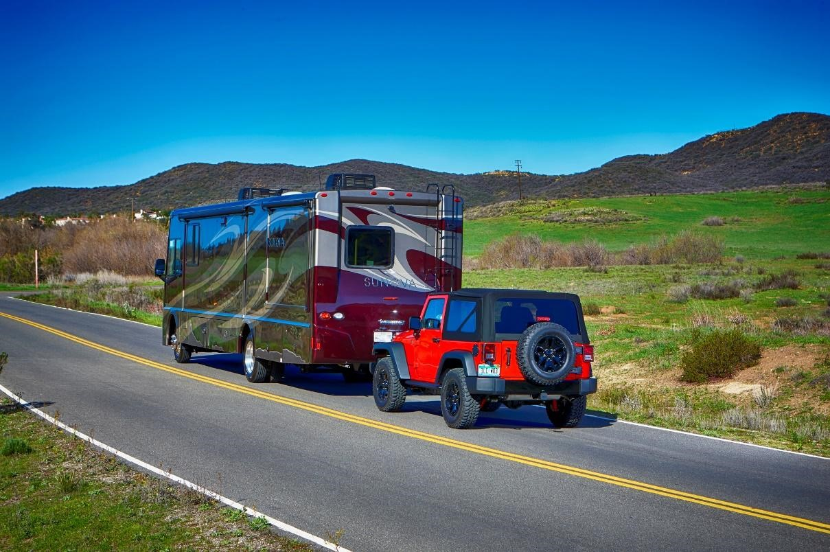 Class A RV towing a Jeep