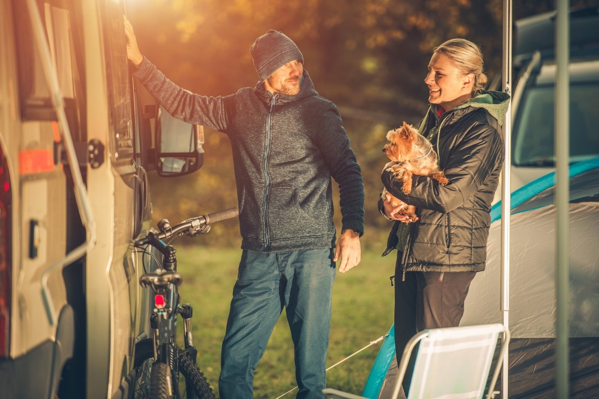 Couple enjoying an RV trip with their dog