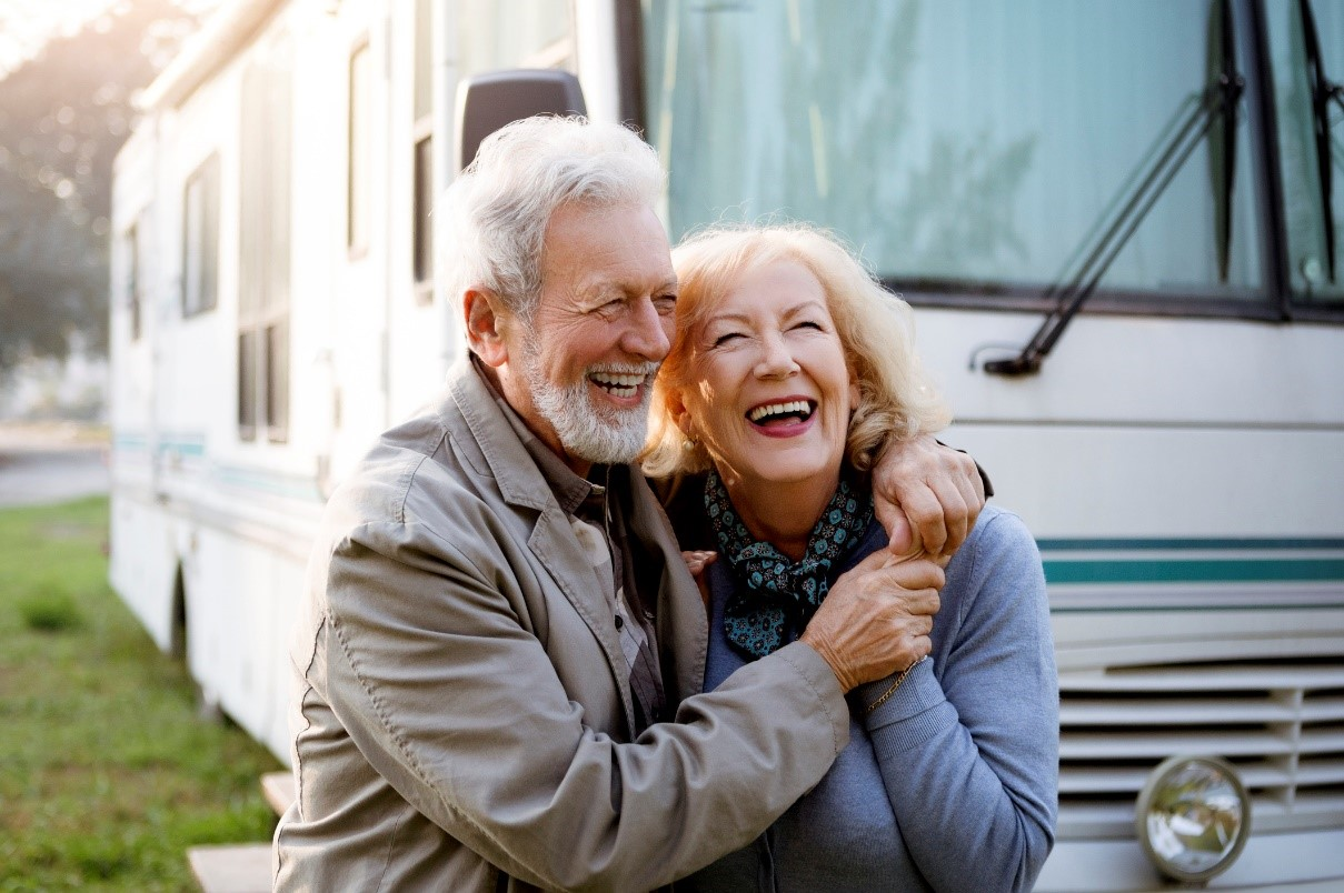 Older couple smiling in front of a Class A motorhome