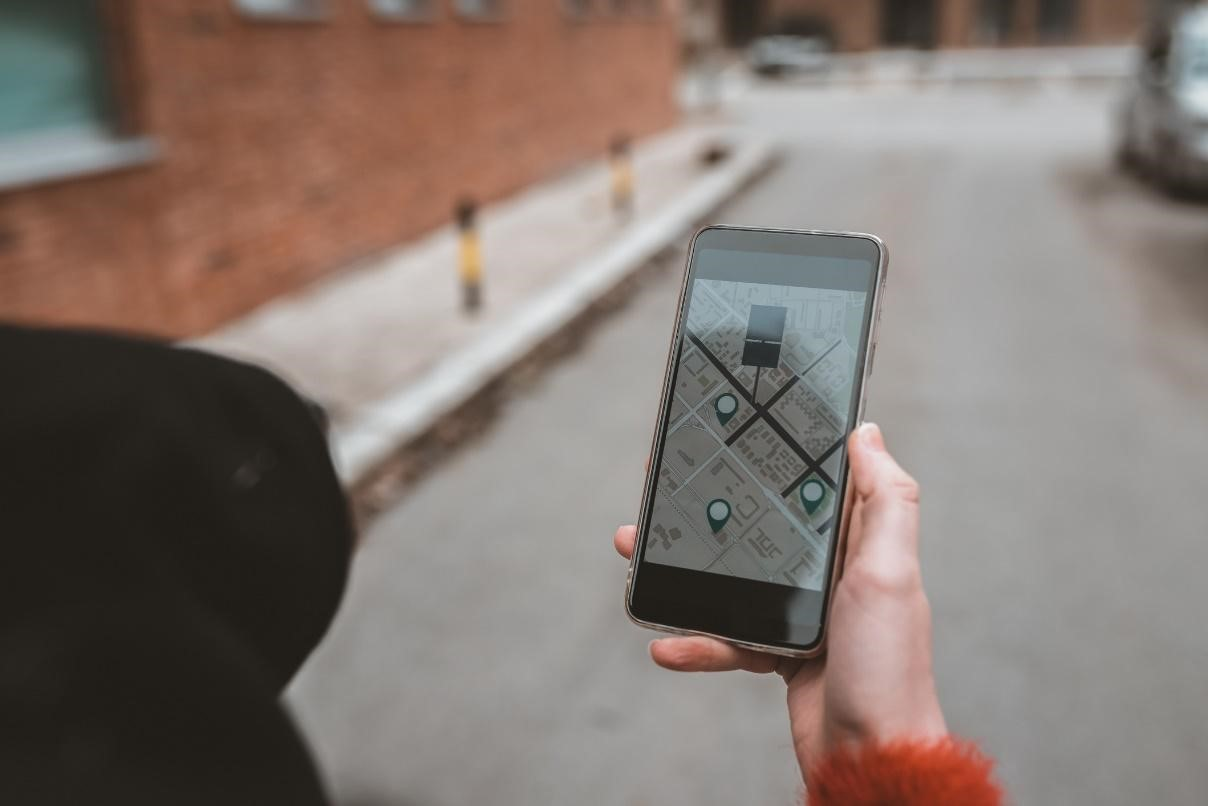 person holding their phone with a maps app open