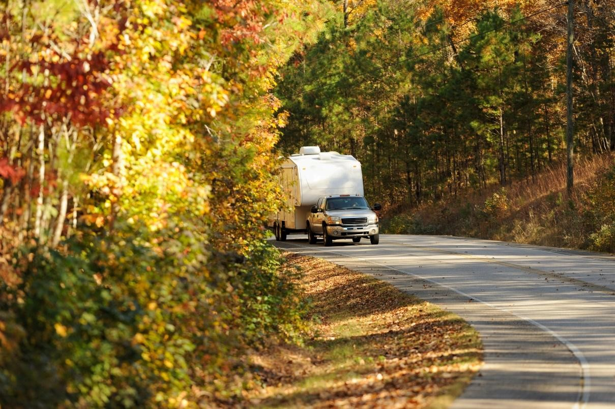 pick up truck towing a travel trailer on a road lined with fall trees