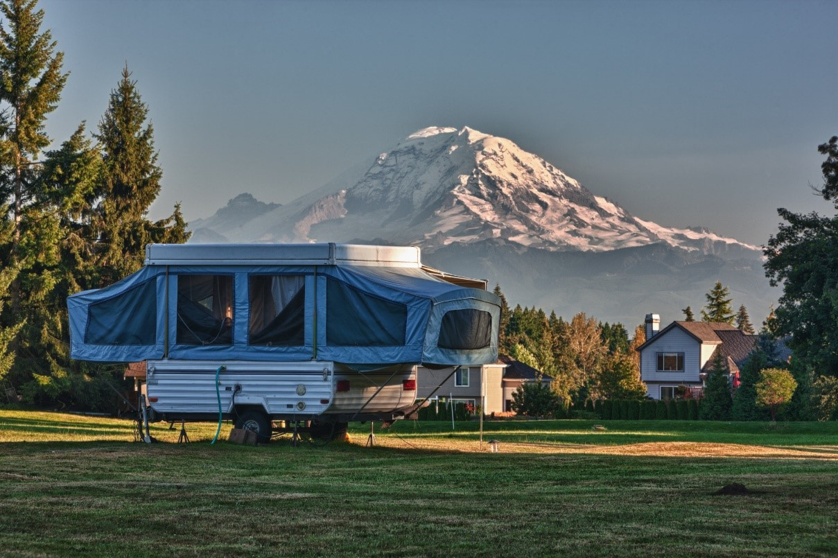 Pop-up camper parked in the shadow of a mountain
