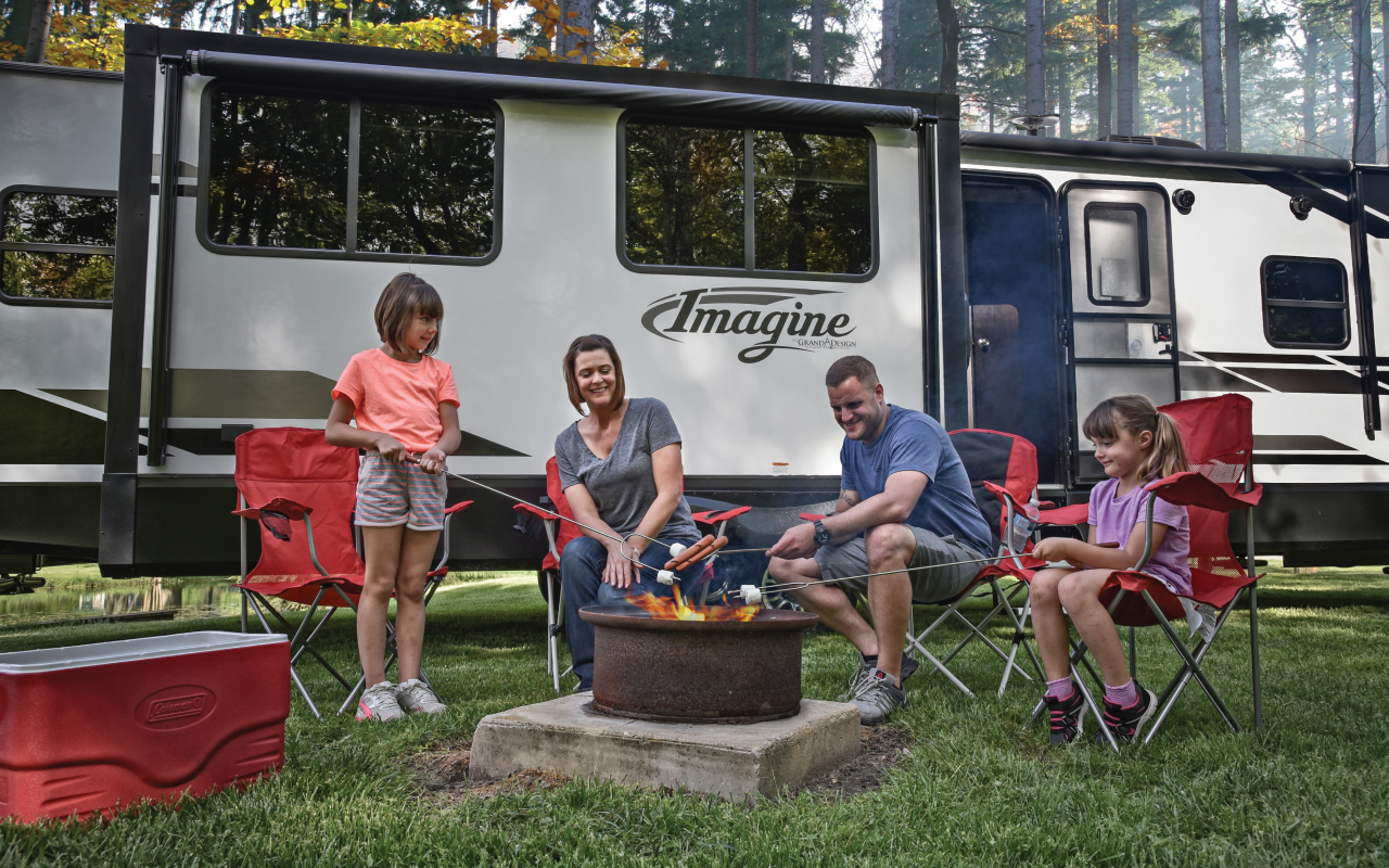 Family roasting food around campfire in front of RV.