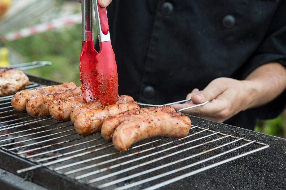 Man grilling sausages on a grill