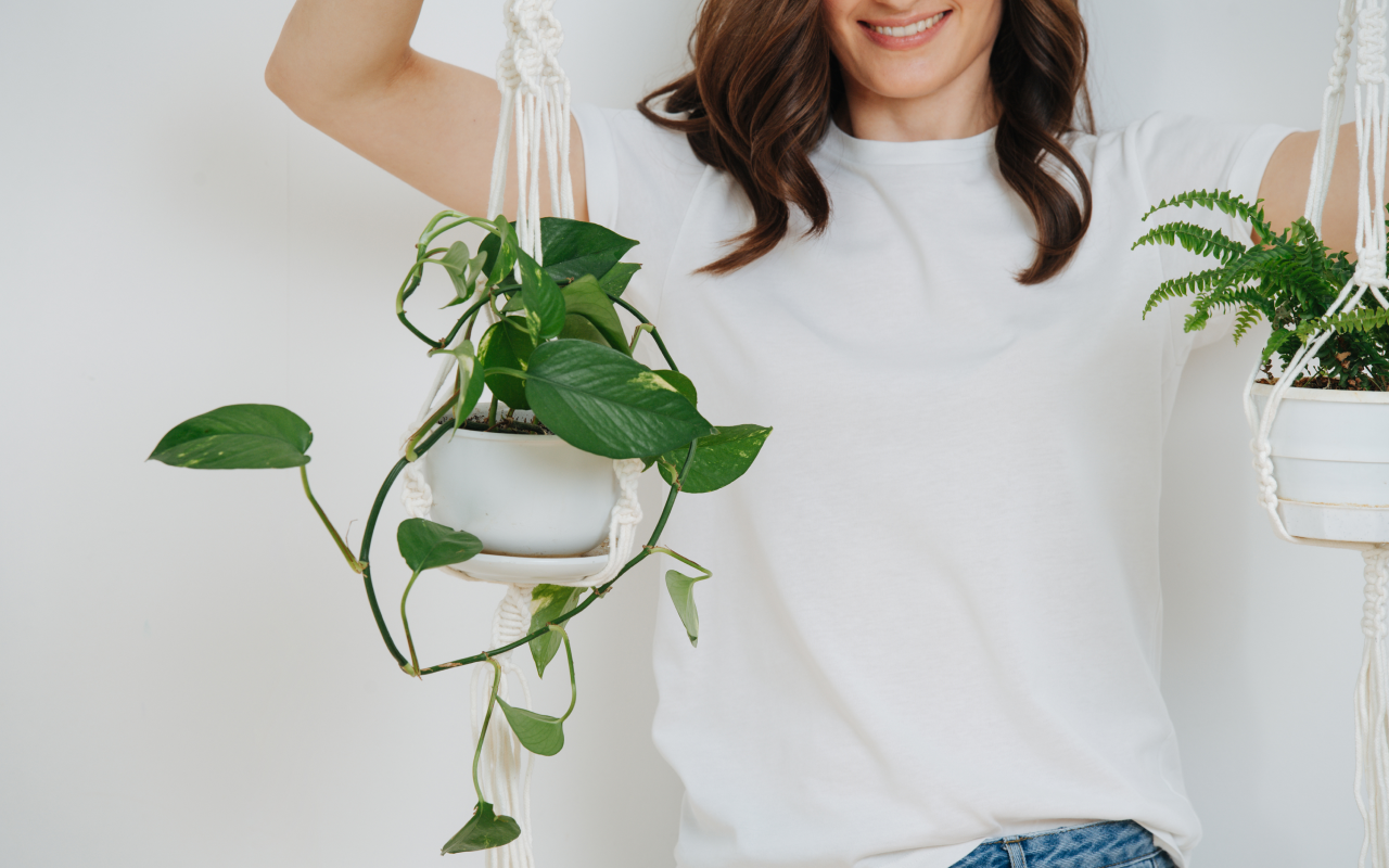 Woman  holding hanging potted plants
